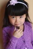 少许吃女孩的亚洲巧克力 免版税库存照片