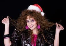 美丽的卷曲女孩朝向圣诞老人 免版税库存图片
