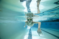 男孩舔游泳在水之下 免版税库存照片