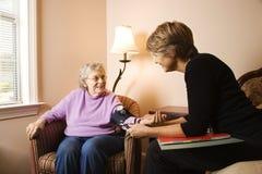 年长的血液有压被采取的妇女 免版税库存照片