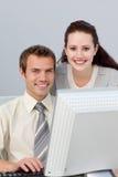 帮助她微笑的女实业家同事 免版税库存照片