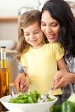 帮助她的母亲的深色的女儿准备沙拉 库存图片