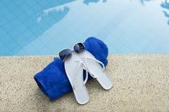 голубой бассеин обувает воду полотенца солнечных очков Стоковая Фотография RF