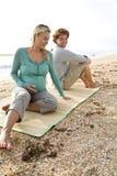 детеныши усаживания циновки пар пляжа супоросые Стоковое фото RF