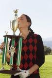 女性高尔夫球运动员亲吻的战利品 免版税库存照片