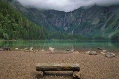 长凳在木附近的湖山 免版税库存照片