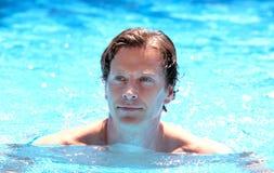 变老的英俊的人中间室外池游泳 免版税图库摄影