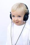 佩带年轻人的男孩愉快的耳机 免版税库存图片