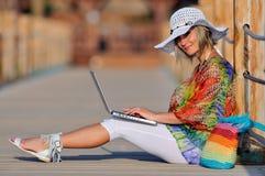 使用妇女的膝上型计算机室外夏天 免版税库存图片