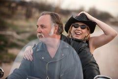 夫妇离开成熟摩托车骑马 库存照片