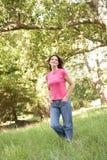 Νέα γυναίκα που περπατά μέσω του πάρκου Στοκ φωτογραφία με δικαίωμα ελεύθερης χρήσης