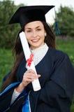 女孩毕业生愉快的兴高采烈的年轻人 免版税库存图片