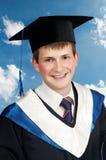 男孩毕业生愉快的面带笑容 免版税库存照片
