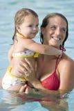 女孩一点母亲池游泳 免版税库存图片