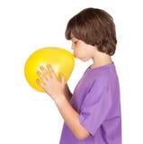 желтый цвет мальчика воздушного шара дуя смешной поднимающий вверх Стоковое Изображение