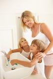 Μητέρα και παιδιά που βουρτσίζουν τα δόντια στο λουτρό Στοκ Φωτογραφία