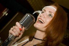 话筒唱歌的妇女 免版税库存照片