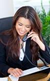 微笑的亚裔女实业家联系在电话 免版税库存照片