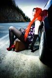 在手提箱附近的可爱的汽车女孩 免版税库存照片