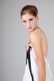 Νέα γυναίκα που κρατά το μέτωπο του φορέματός της Στοκ Εικόνες