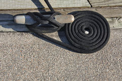 黑色磁夹板卷起的码头绳索 库存照片