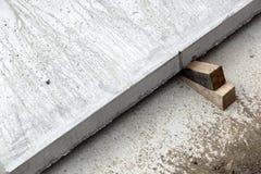 混凝土板楔住木头 免版税库存图片