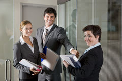 Τρεις εργαζόμενοι γραφείων στην πόρτα της αίθουσας συνεδριάσεων Στοκ Φωτογραφίες