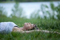 детеныши женщины поля счастливые лежа Стоковое Изображение