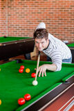 演奏落袋撞球的断言的年轻人 免版税图库摄影
