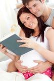 相当孕妇和她的丈夫读取 免版税库存图片