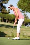 Ανώτερος θηλυκός παίκτης γκολφ στο γήπεδο του γκολφ Στοκ Φωτογραφίες