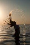 女孩头发她的飞溅水的海运 免版税图库摄影