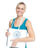 Καυκάσια νέα γυναίκα που κρατά μια κλίμακα βάρους Στοκ Εικόνες
