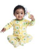 演奏吵闹声微笑的女婴 免版税库存图片