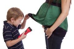 查找妈妈怀孕的衬衣的男孩下 免版税库存照片