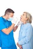 доктор рассматривает старшее горло Стоковое фото RF