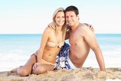 享用节假日年轻人的海滩夫妇 免版税库存图片