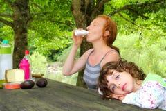 女儿母亲室外公园野餐 免版税库存图片