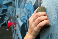 上升五颜六色的暂挂的登山人了解墙&# 免版税图库摄影