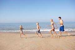 Νέα οικογένεια που τρέχει στην παραλία Στοκ Εικόνες