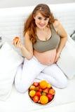 拿着怀孕的微笑的妇女的果子现有量 库存照片