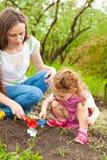女儿庭院帮助的妈妈 免版税图库摄影
