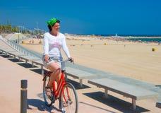 骑自行车她的骑马妇女年轻人 免版税库存图片