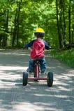 男孩少许骑马三轮车 免版税库存照片