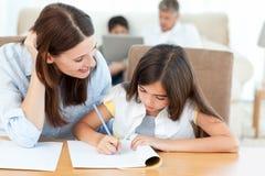 帮助她的她的家庭作业的母亲女儿 库存照片