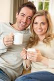 夫妇放松的坐的沙发年轻人 免版税库存照片