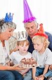 吹在生日蛋糕的子项 免版税库存照片