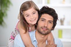 拥抱小人微笑的年轻人的女孩 免版税库存照片