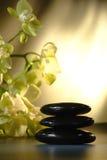 камни массажа пирамиды из камней горячими отполированные орхидеями Стоковое фото RF