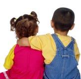 在一起坐女孩的孩子附近的胳膊 免版税库存图片